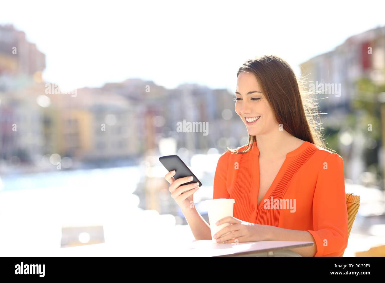 Felice lady utilizza un telefono intelligente in un caffè di una città costiera in vacanza Immagini Stock