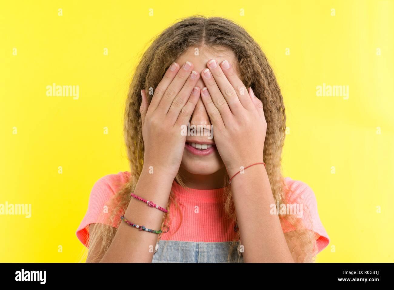 Ragazza adolescente con ricci capelli biondi il viso coperto con le mani, luminoso giallo di sfondo per studio. Immagini Stock