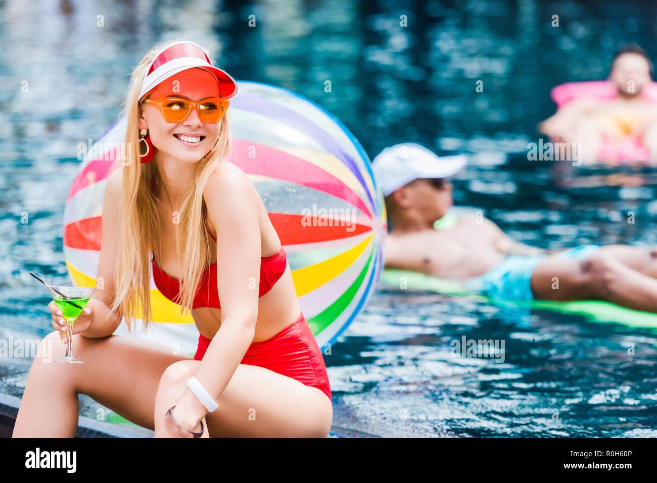 Bella giovane donna in costume da bagno seduta vicino alla piscina e bere cocktail Immagini Stock