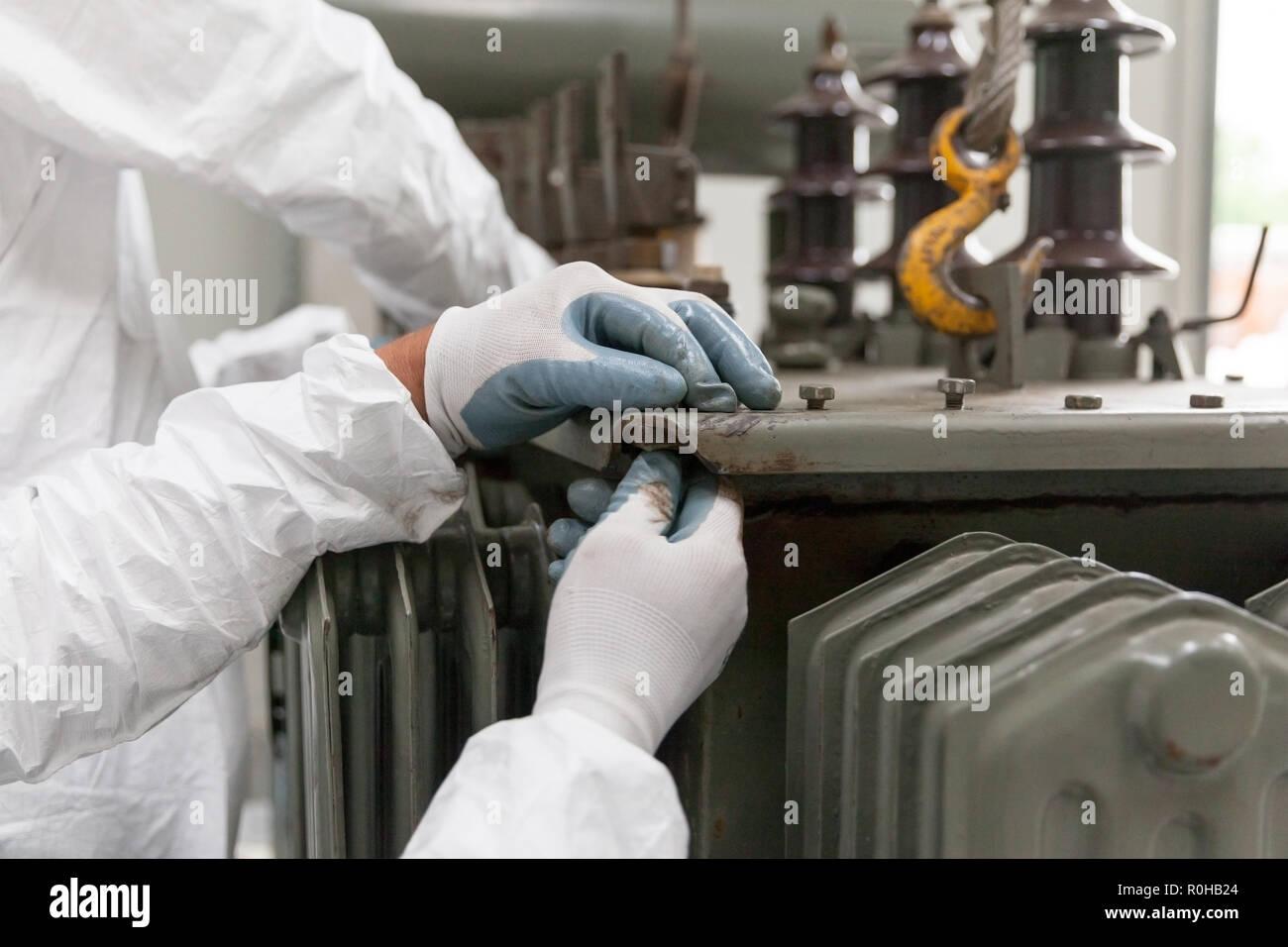 Un uomo in bianco protettivo di indumenti da lavoro e guanti, la preparazione di un vecchio trasformatore di componenti per il riciclaggio. Gestione dei rifiuti Immagini Stock
