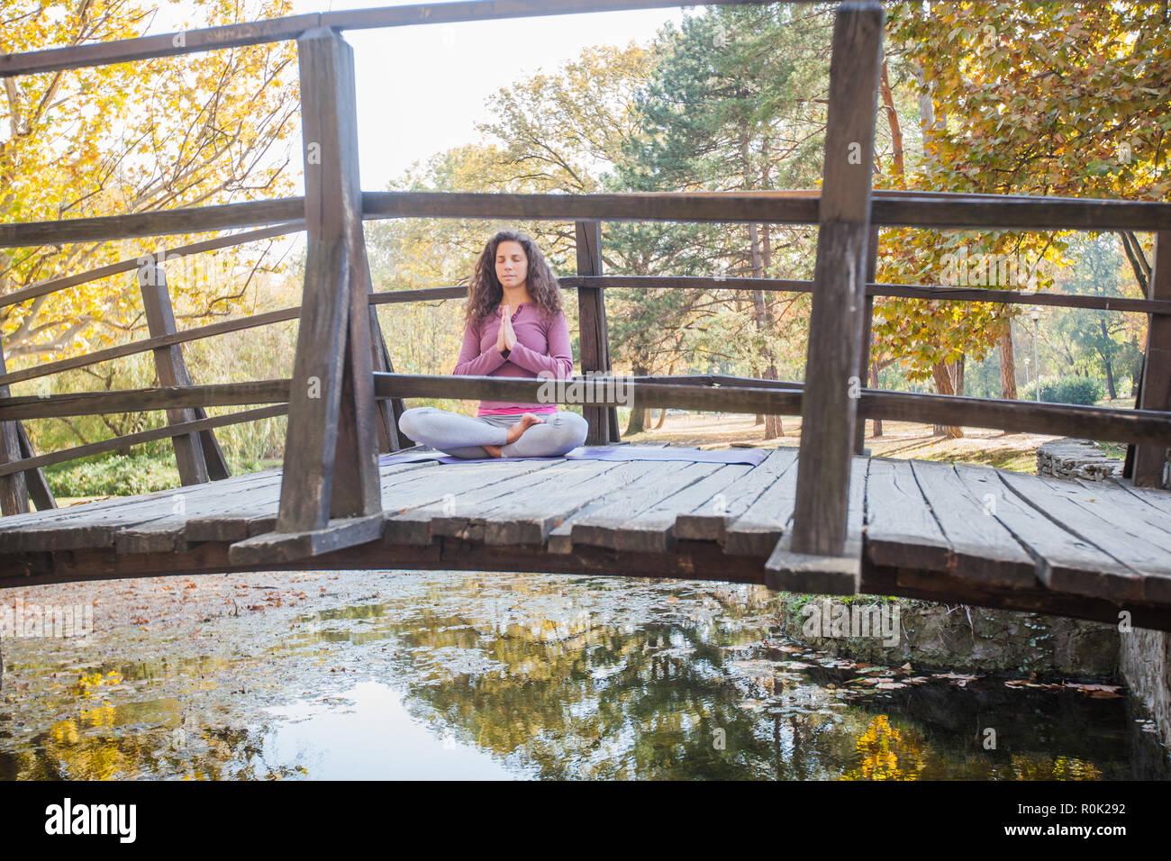 Bella giovane donna in una posa meditativa sul ponte di legno al parco. Sani di sesso femminile facendo esercizi yoga padmasana, Lotus pongono, Autunno mattina di sole. Foto Stock