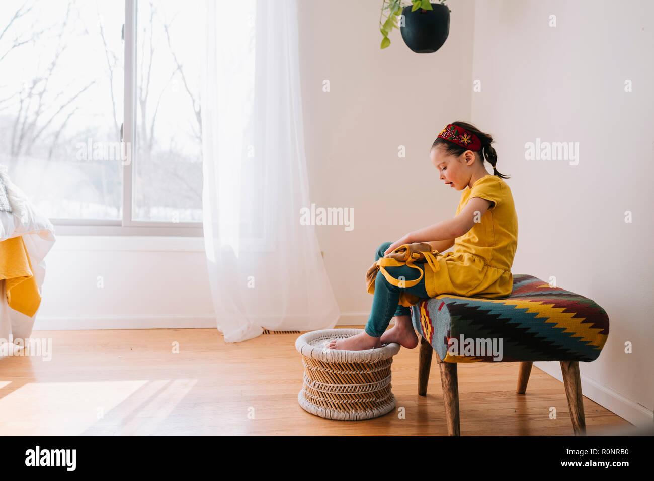 Ragazza seduta su uno sgabello chiudendo il suo zaino foto