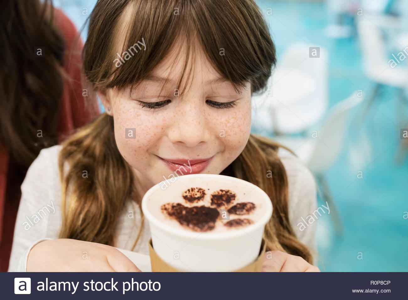 Curioso ragazza di bere cioccolata calda con zampa di schiuma di stampa a cat cafe Immagini Stock