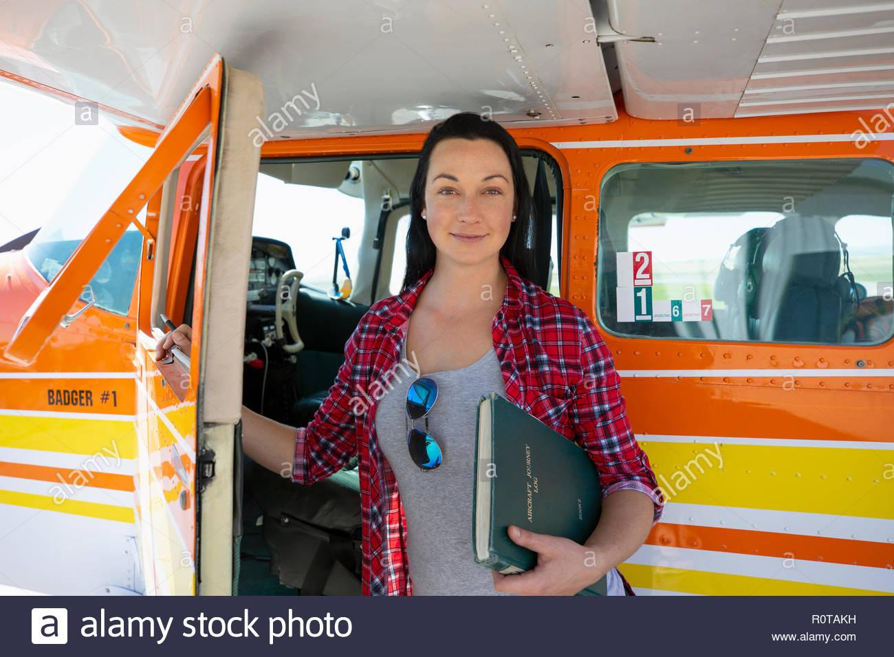 Ritratto sorridente e fiducioso pilota femmina permanente al propellor aeroplano Immagini Stock