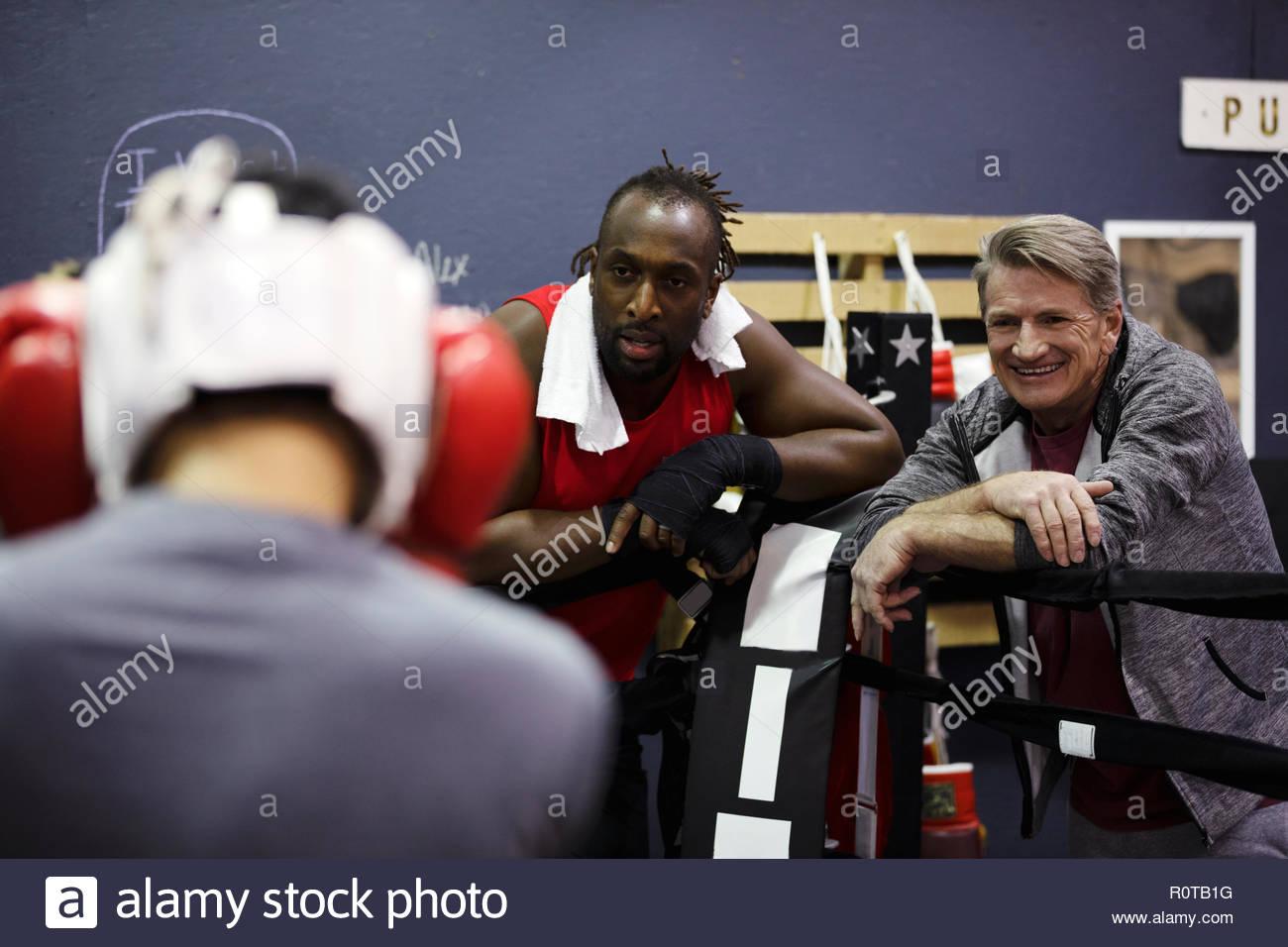 Boxer maschio e il trainer in palestra Immagini Stock