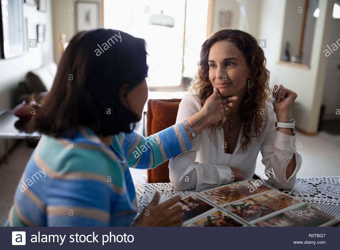 Affettuosa Latinx la figlia e la madre senior guardando album di foto Immagini Stock
