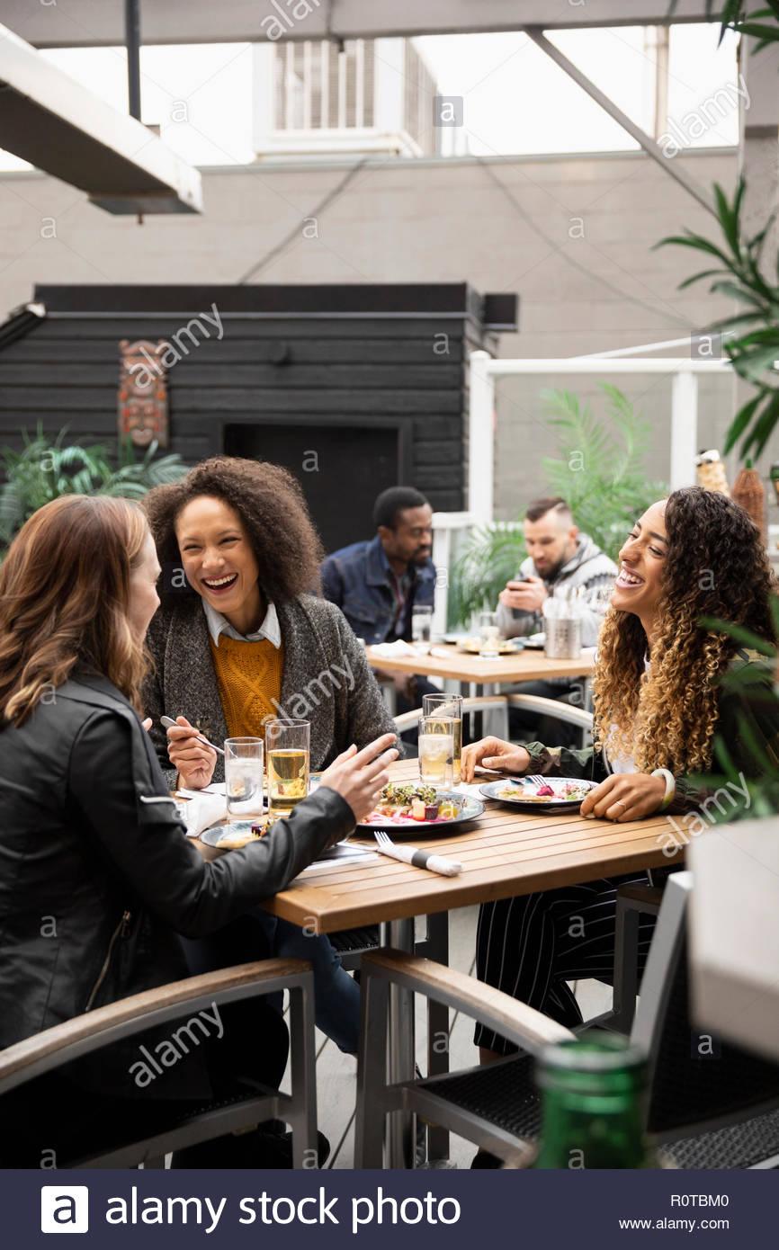 Donne che ridono amici gustando il pranzo sul patio cafe Immagini Stock