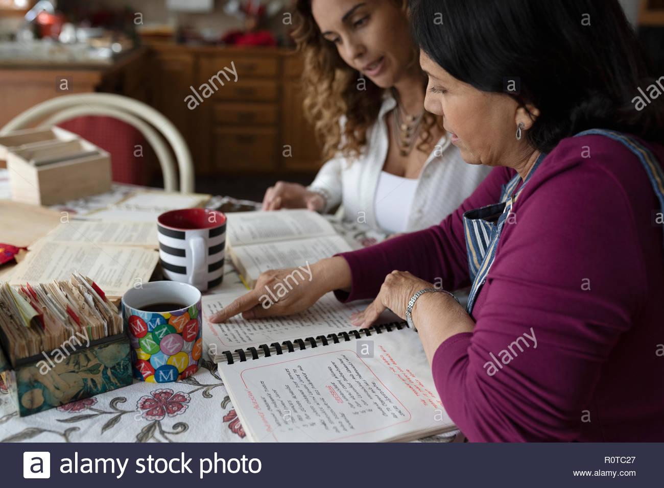 Latinx la figlia e la madre senior guardando il libro di ricette di cucina Immagini Stock
