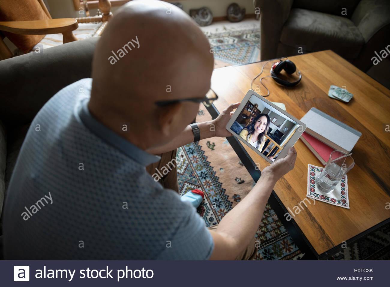 Latinx uomo video chat con la donna sulla tavoletta digitale Immagini Stock