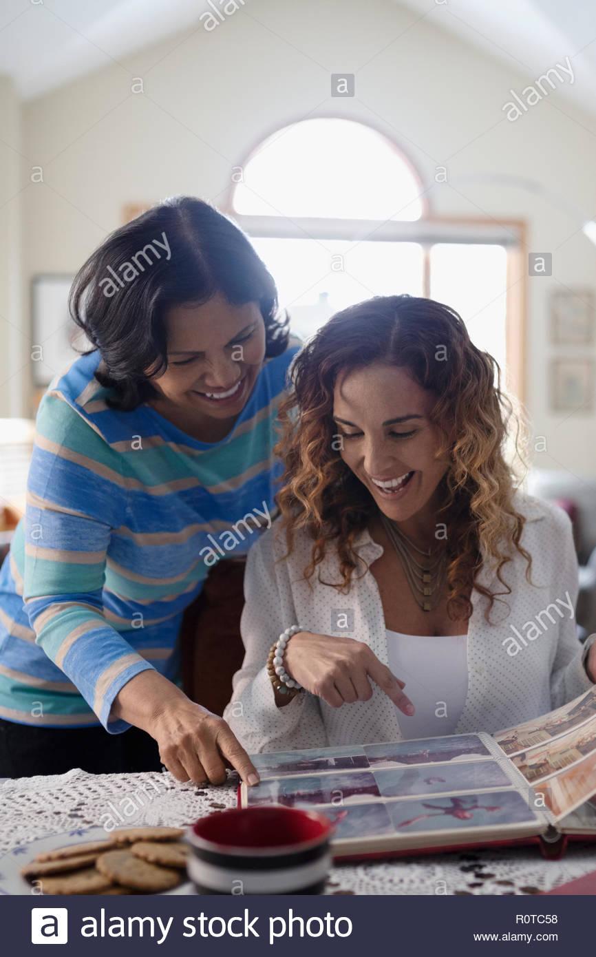 Latinx la figlia e la madre senior guardando album di foto Immagini Stock