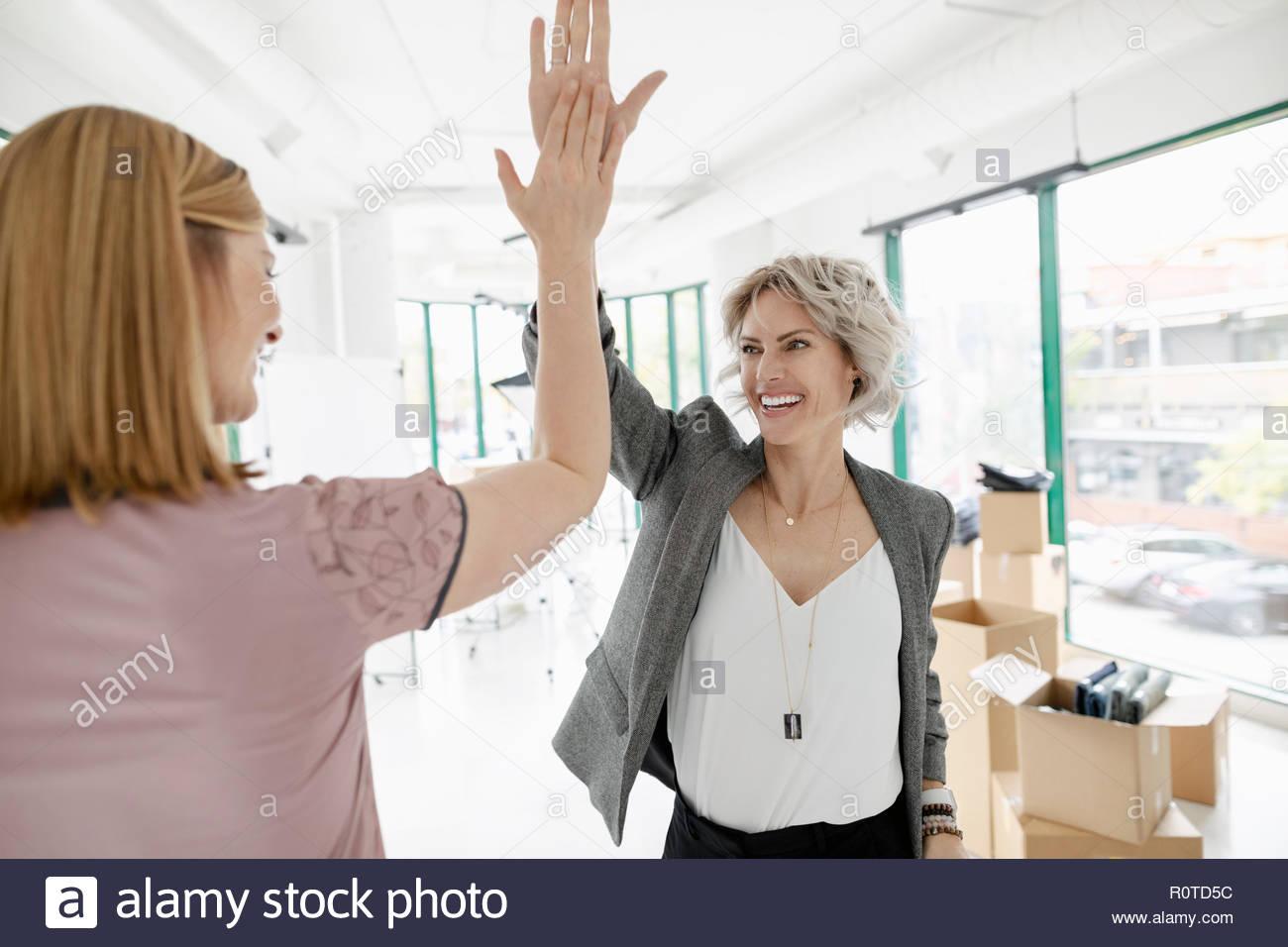 Femmina eccitato i proprietari di affari ad alta fiving nel nuovo spazio di vendita Immagini Stock
