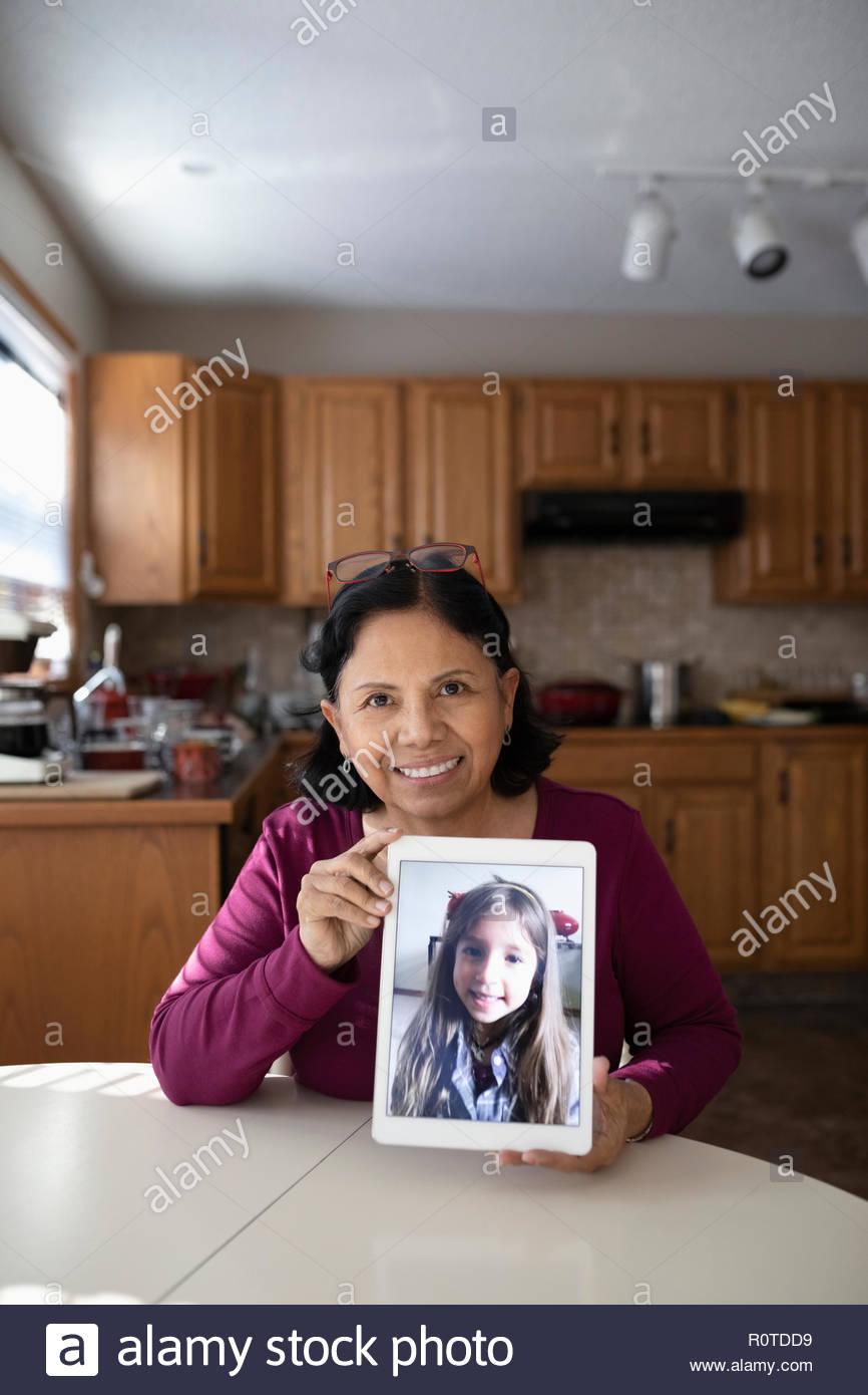 Ritratto fiducioso Latinx nonna le chat video con la nipote sulla tavoletta digitale Immagini Stock