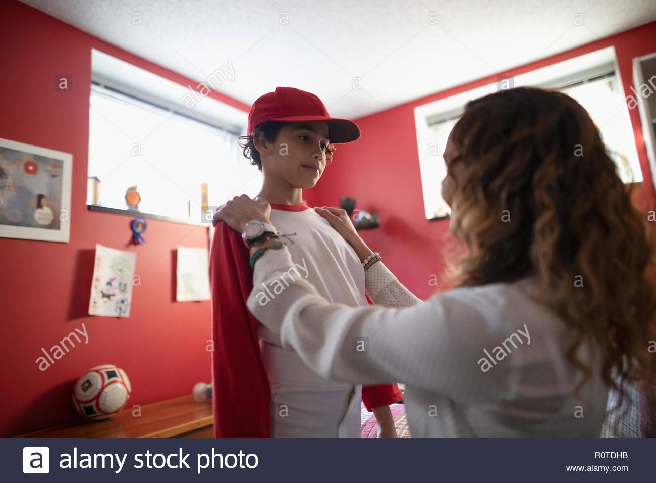 Madre Latinx aiutando figlio vestirsi per pratica di baseball in camera da letto Immagini Stock