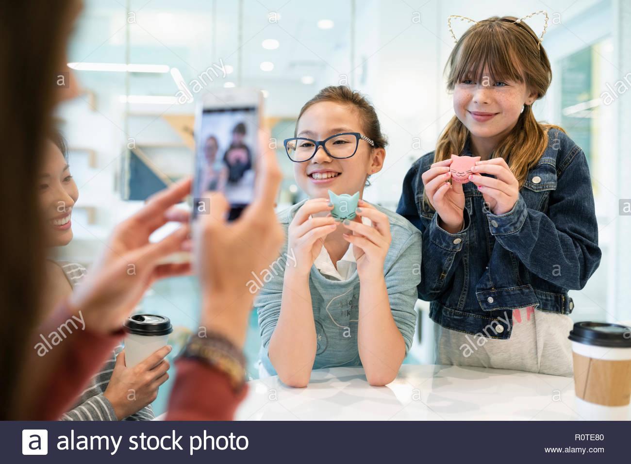 Le ragazze che posano per una fotografia con un gattino i cookie in cat cafe Immagini Stock