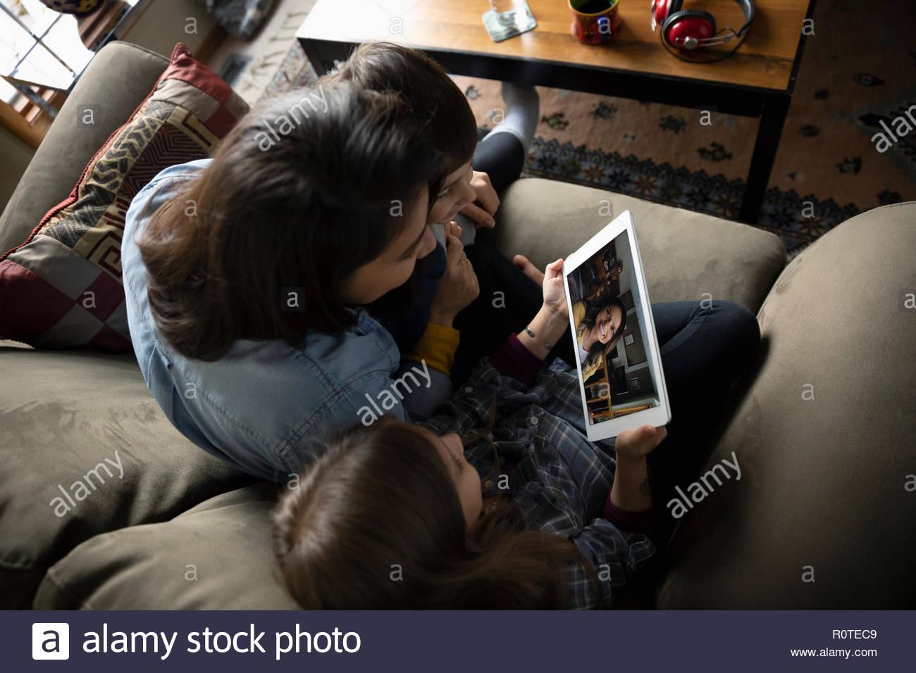 Famiglia Latinx le chat video con tavoletta digitale sul divano Immagini Stock