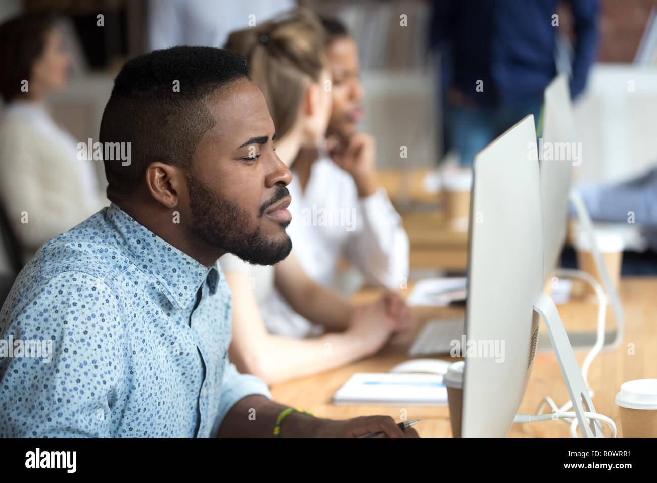 Riflessivo African American guardare lo schermo del computer funzionante Immagini Stock