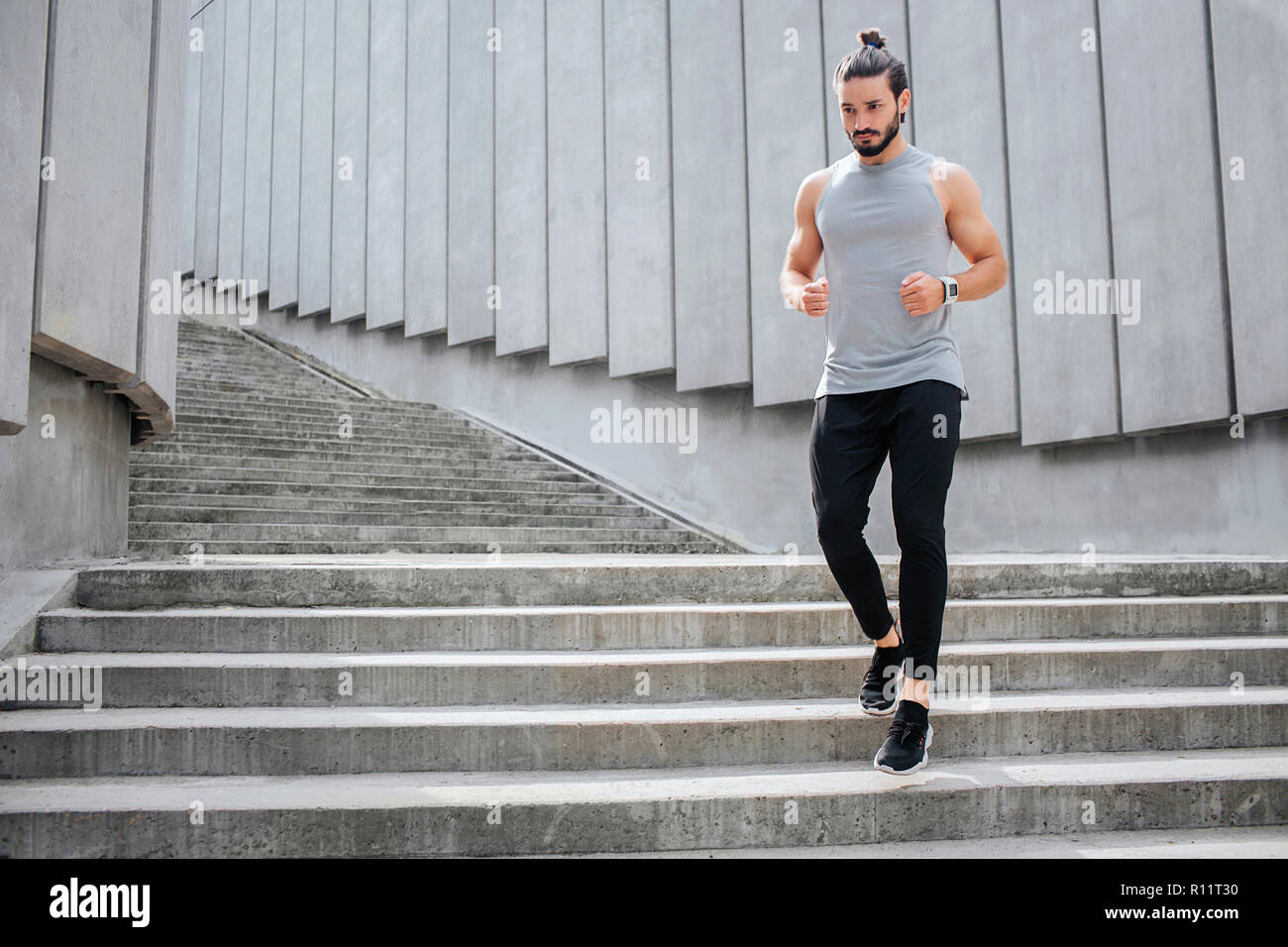 Giovane uomo jogging. Egli corre giù sui gradini. Muscoloso e ben costruito l uomo è grave e concentrata. Egli indossa uniformi sportive Immagini Stock