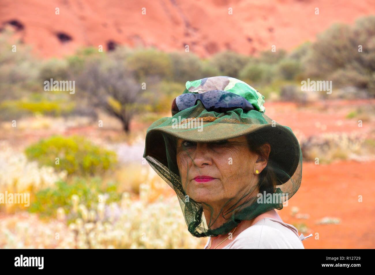 Brunette donna nell'entroterra australiano protetto con una zanzariera oltre il cappello e la testa. Immagini Stock