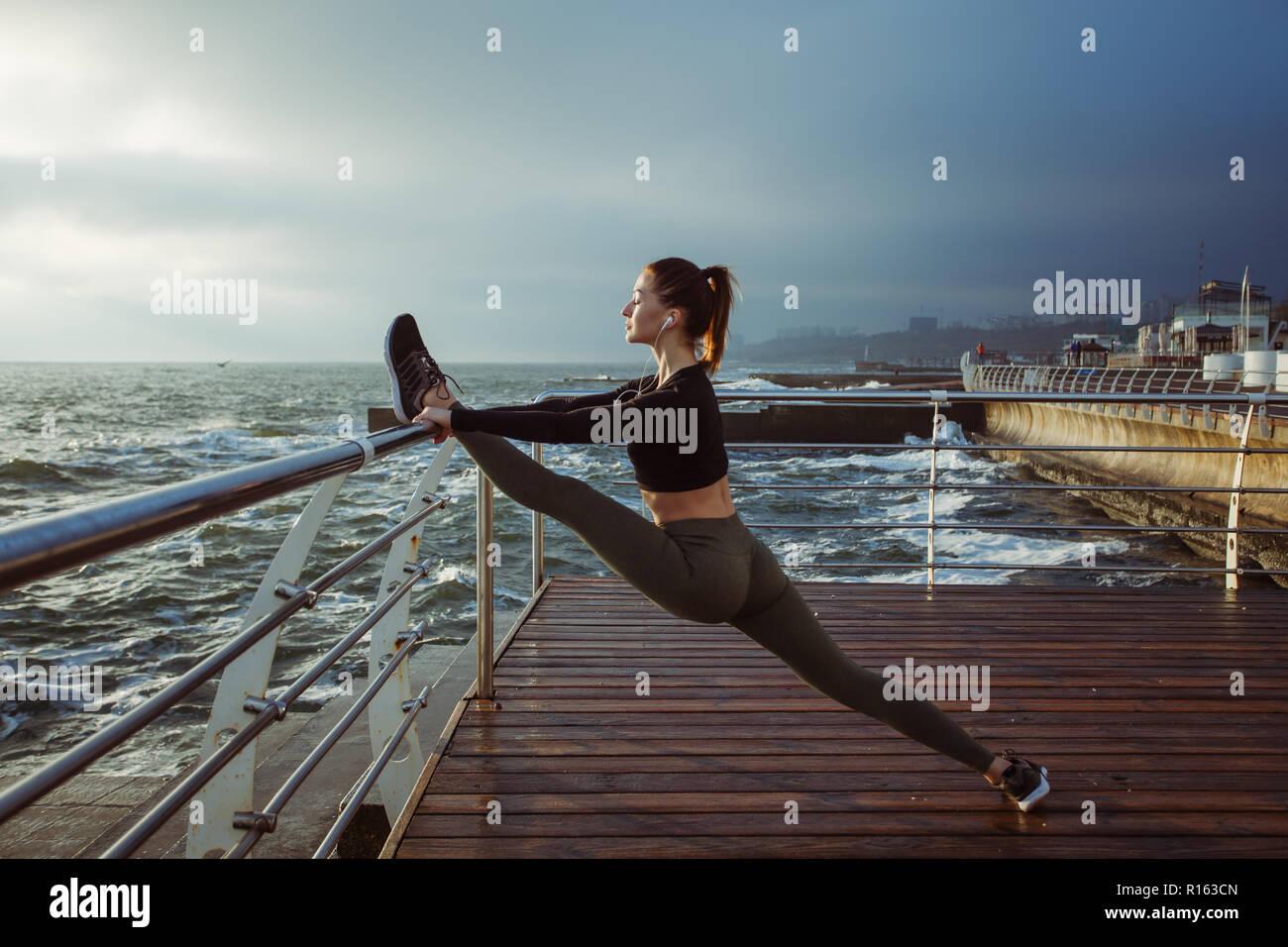 Modello di fitness atleta ragazza warm up il suo allungamento bicipiti femorali gamba e retro Foto Stock