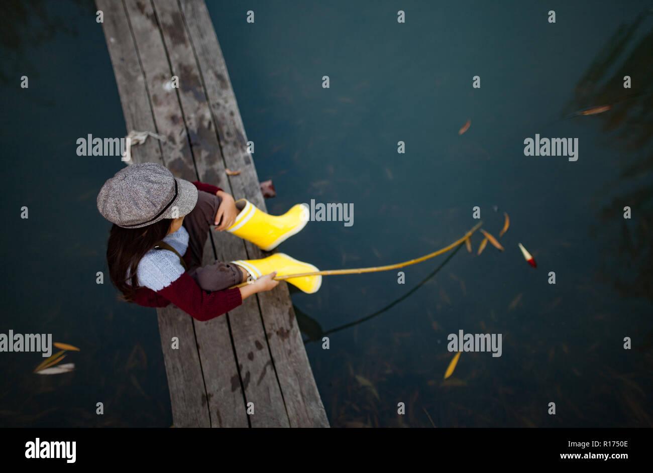 Bambino ragazza in giallo stivali di gomma e cappuccio si siede sul legno ponte di pesca e le catture di pesce con self-made canna da pesca. Vista dall'alto. Foto Stock