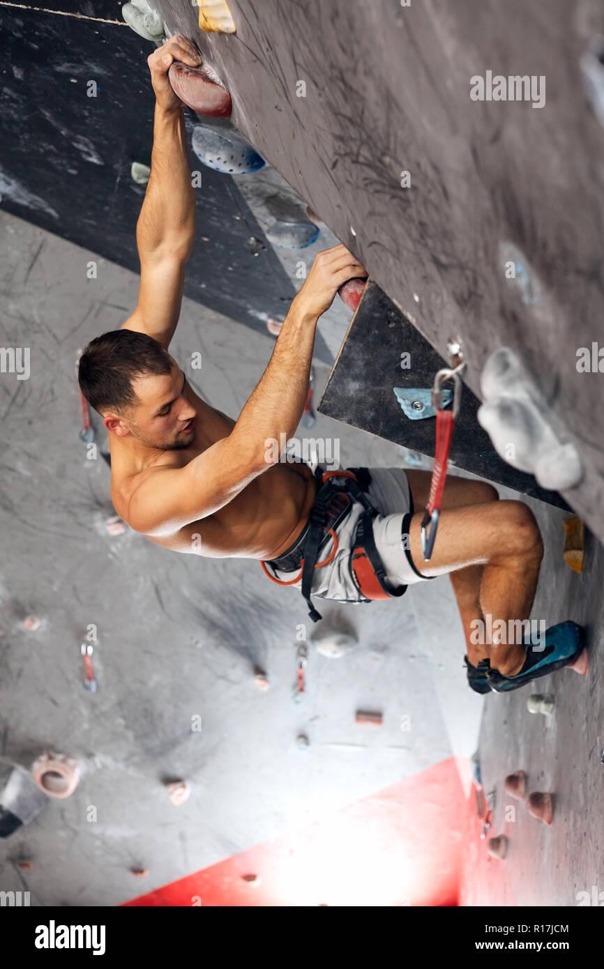 Maschio scalatore professionista in allenamento indoor a bouldering centro. Foto Stock