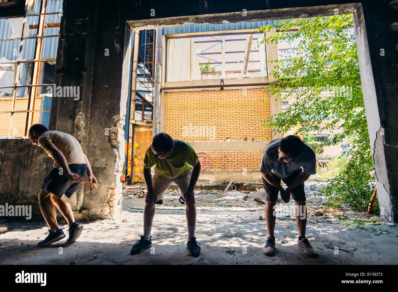 Tre giovani amici formazione parkour durante il salto tra di loro Immagini Stock