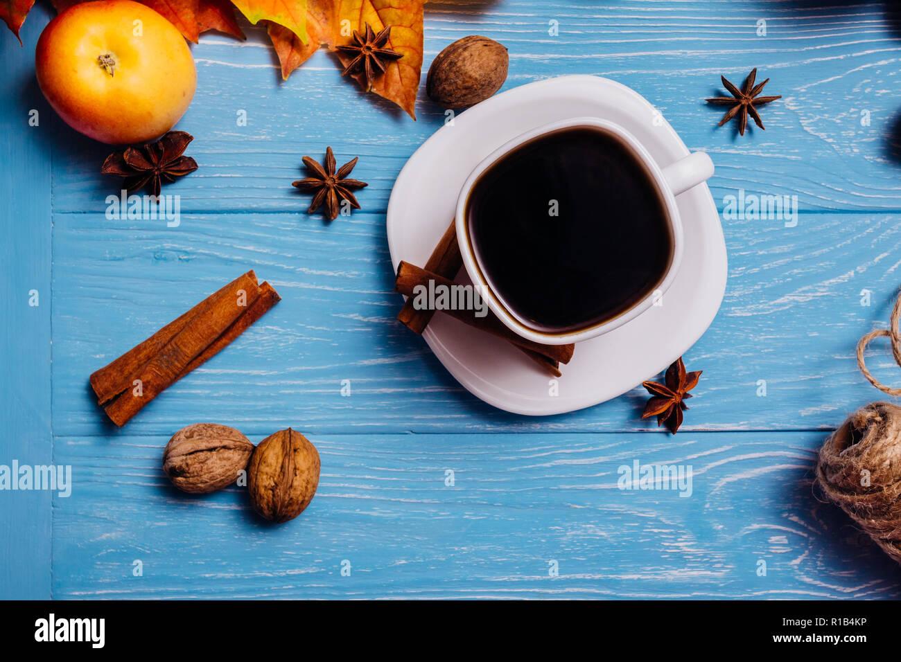 Nero caffè in una tazza bianca su un piattino con cannella noce di anice e Apple su una superficie di colore blu Immagini Stock