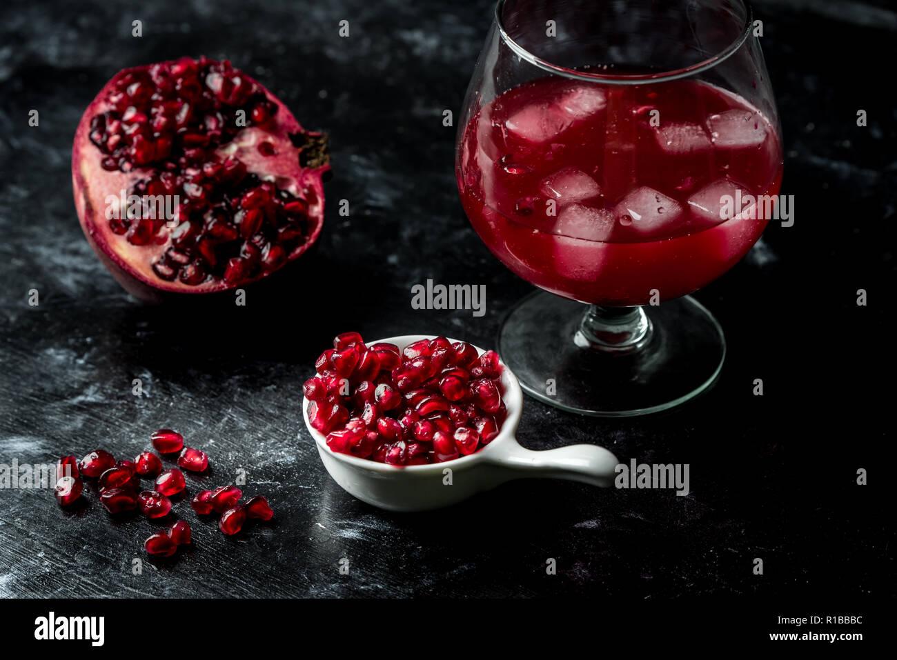 La tentazione di melograno rosso, semi e succo di frutta fresco con l'aggiunta di ghiaccio su un nero, sfondo di pietra Immagini Stock