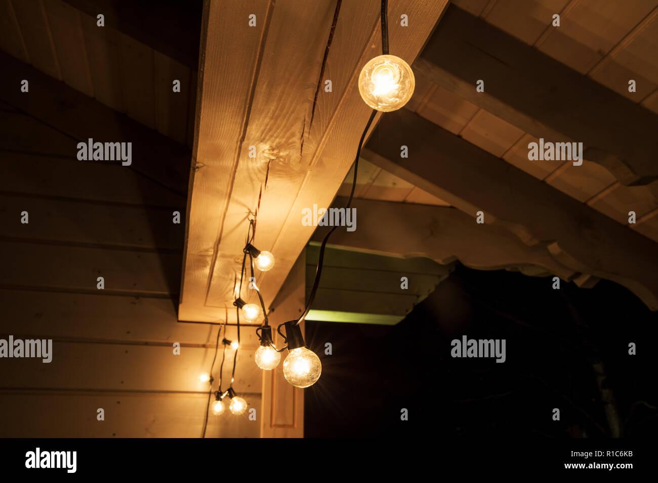 Decorative luci strada appeso sulla terrazza di una casa in legno