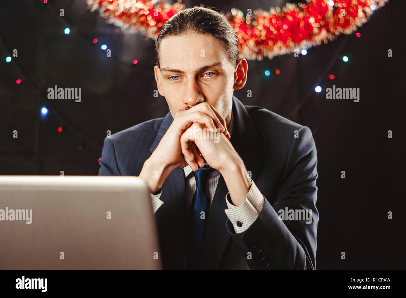 Imprenditore lavora per la Vigilia di Capodanno. Egli era molto stanco e si è addormentato dietro il suo computer portatile. Indossa un cappello di Natale. Foto Stock