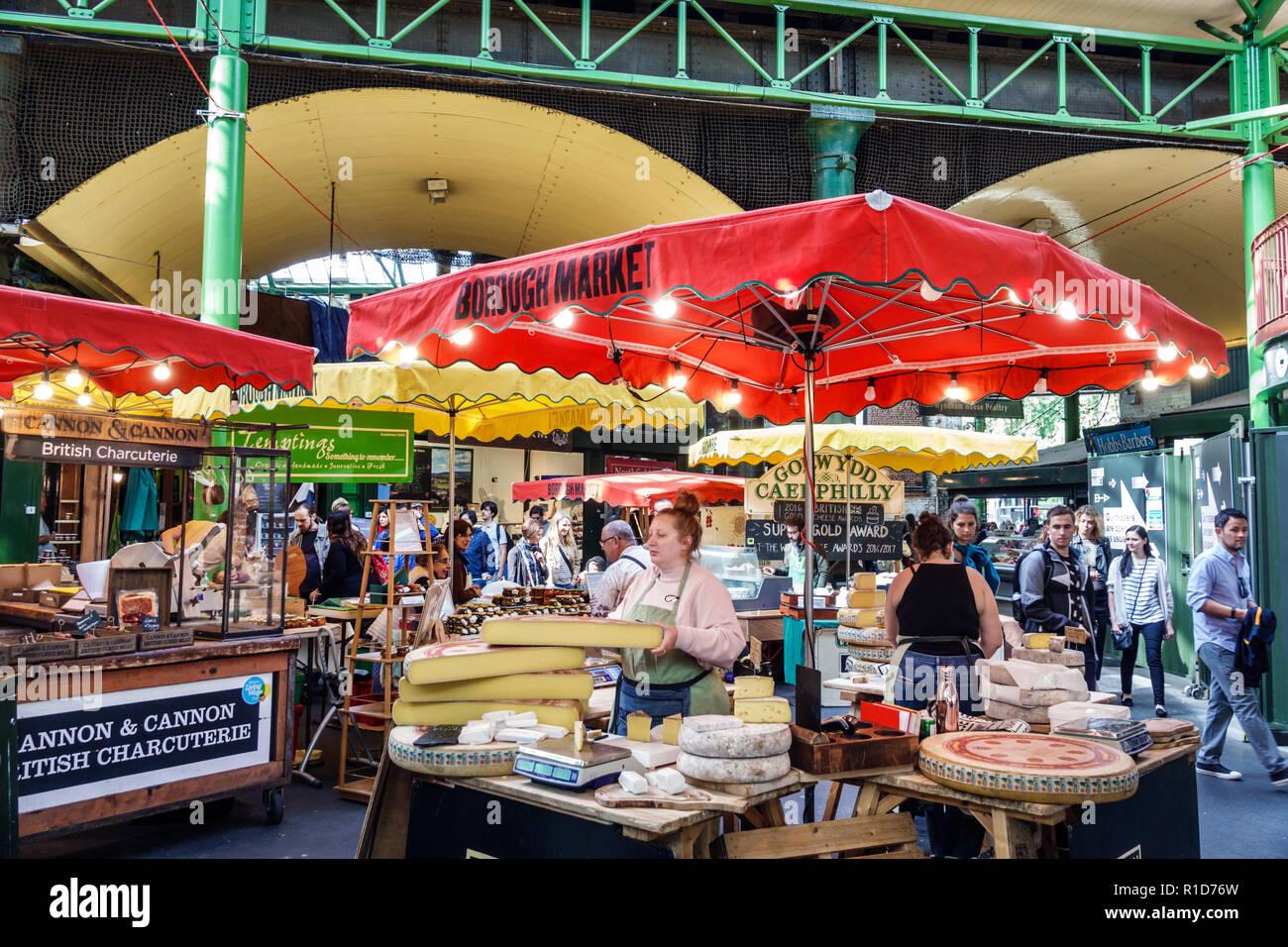 Londra Inghilterra Regno Unito Gran Bretagna South Bank Southwark Borough Market fornitori bancarelle di formaggio artigianale giri ruote donna vendita display Immagini Stock