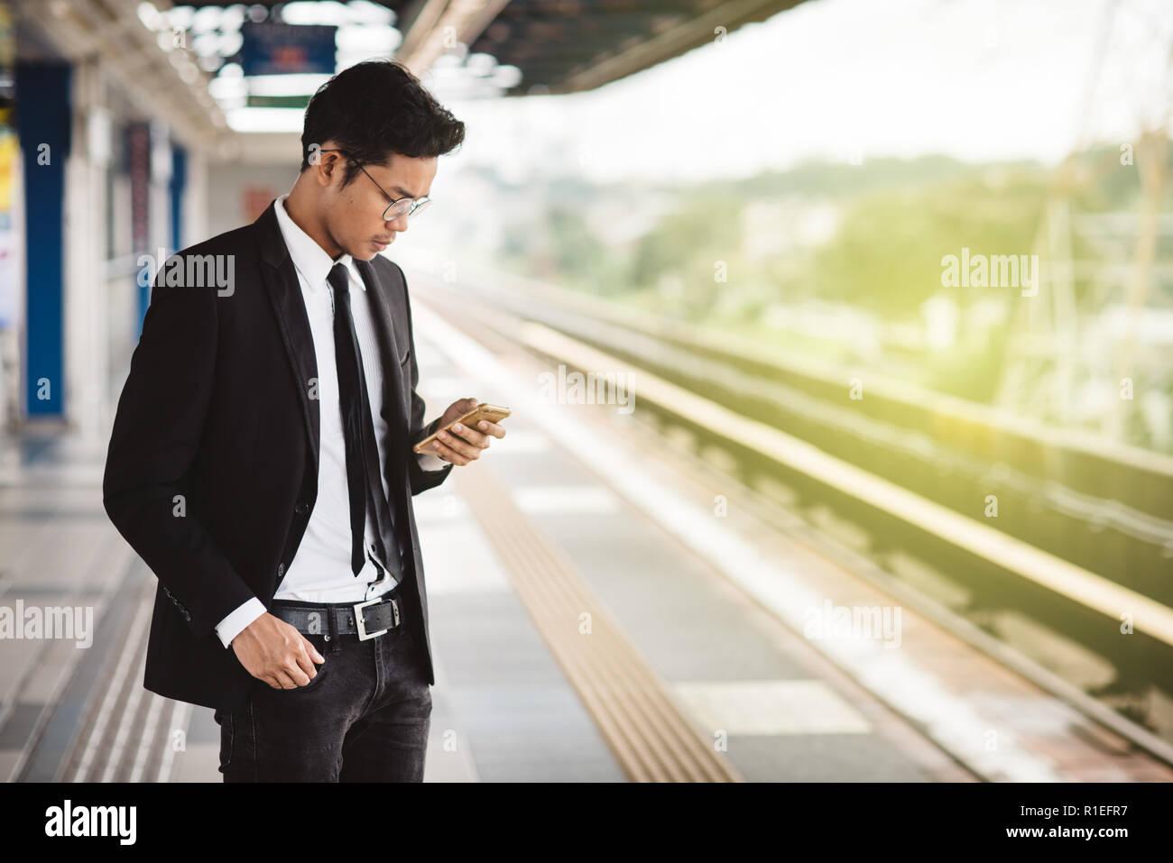 Giovani asiatici imprenditore hipster con lo smartphone in attesa alla piattaforma del treno. Concetto di tecnologia wireless, i trasporti pubblici e il business travel Foto Stock