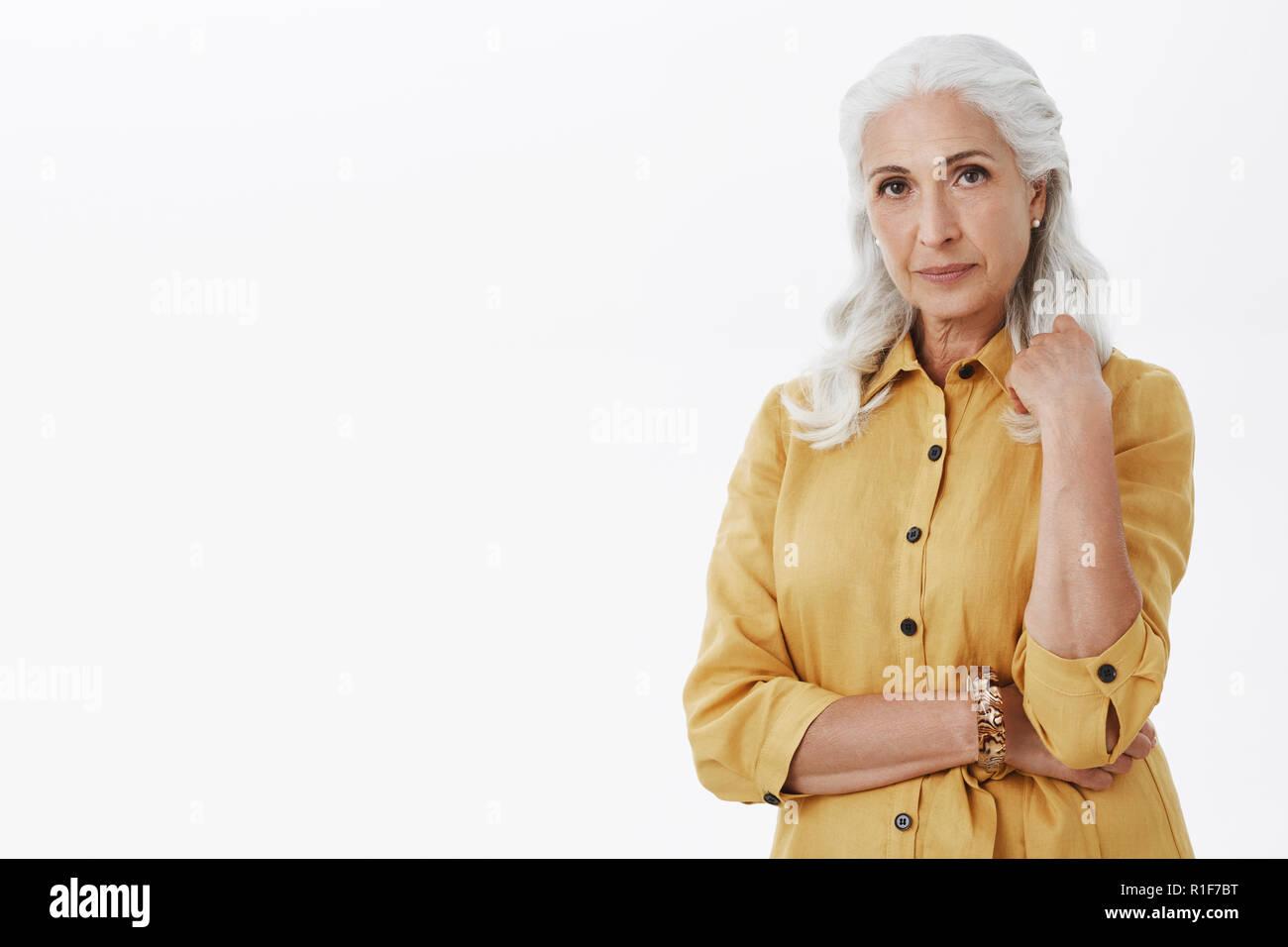 Studio shot di elegante e femminile donna anziana con i capelli bianchi  orecchini perla e giallo 21462f28f833