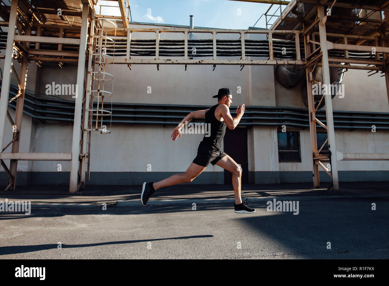 Uomo sportivo corre veloce in città industriale dello sfondo. Sport ed atletica, fitness, attività di jogging Immagini Stock