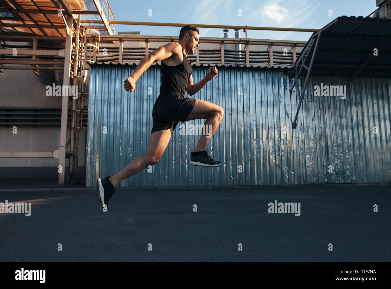 Bel giovane in esecuzione in edificio ndustrial sfondo. runner, jogging, attività fitness Immagini Stock