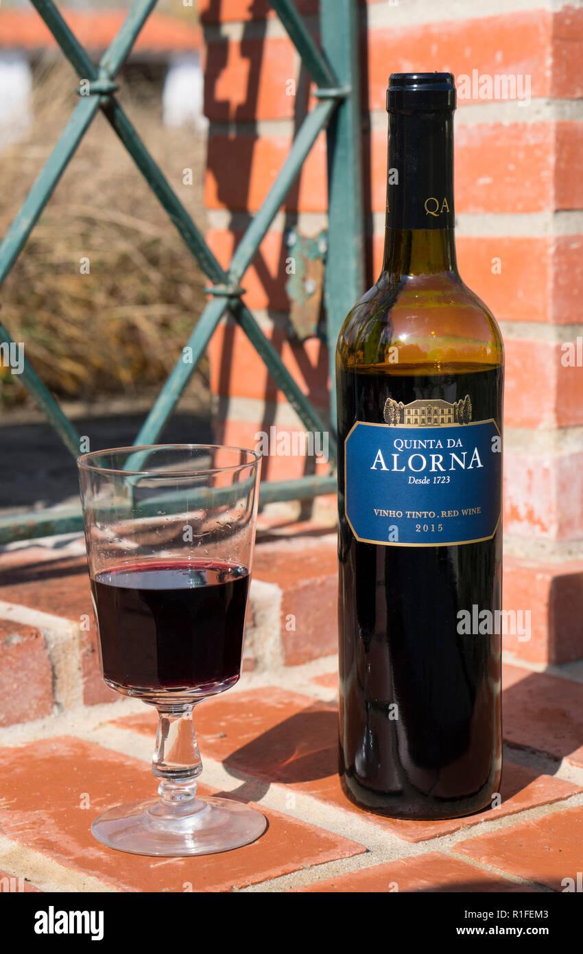 Bottiglia e bicchiere di vino rosso prodotto da uve Tinta Roriz, Castelão, Syrah e Alicante Bouschet. Questo vino rosso rivela di frutta rossa matura aromi. Foto Stock
