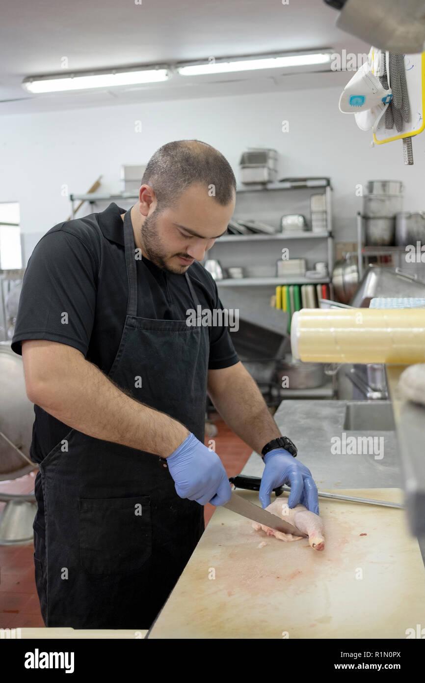 Un israeliano residente di un kibbutz di Kfar HaRuv nel Golan opere in lKitchen preparazione della carne di pollo per il pasto serale. Immagini Stock