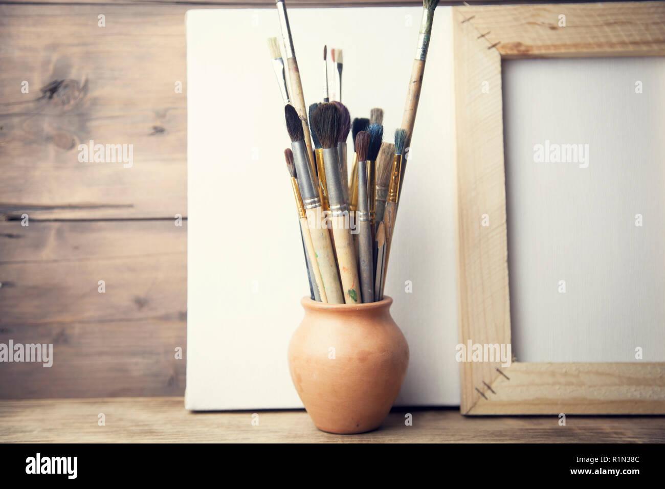 Pennelli per dipingere in tela bianca su sfondo di legno foto