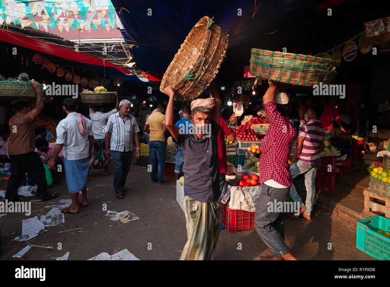 """Facchini in mercato Crawford, Mumbai, India, ora ufficialmente chiamato mahatma Jyotiba Phule Mandai, il loro equilibrio """"palti' o cestelli sopra le loro teste Immagini Stock"""