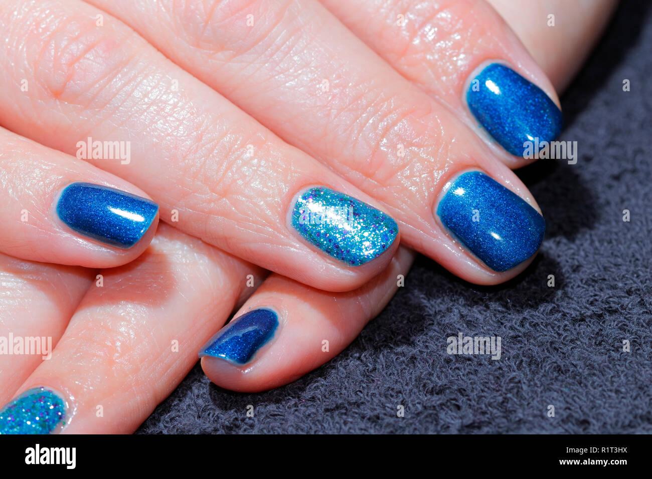 Blu scintillanti glittery unghie dopo appena essendo applicato in una manicure. Immagini Stock