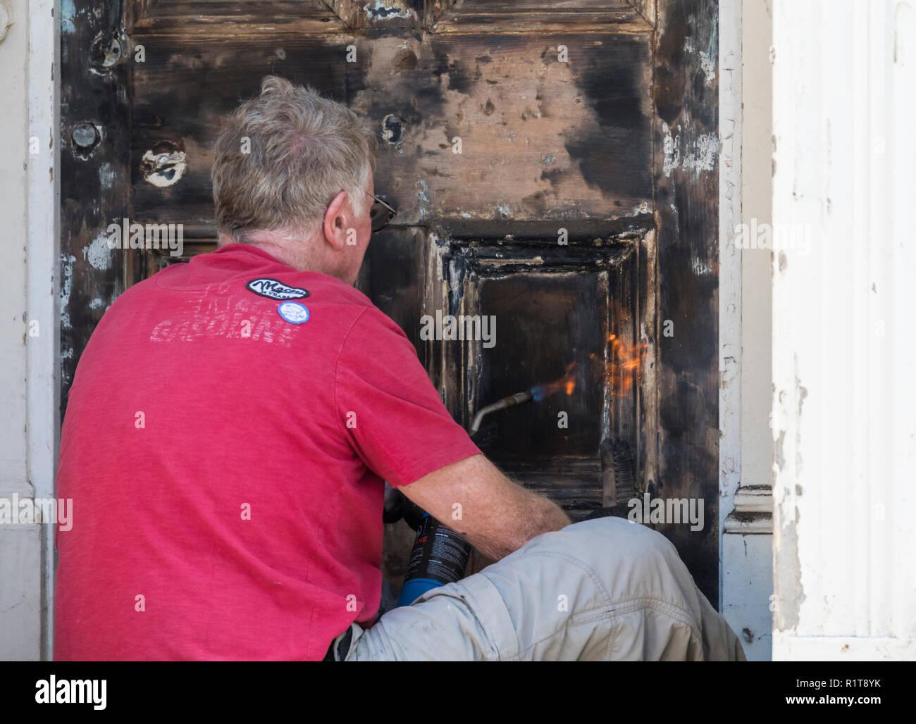 Uomo che utilizza gas caldo blow torcia (cannello) alla striscia di vernice da una porta anteriore. Assemblea rinnovi, pittore e decoratore. Immagini Stock