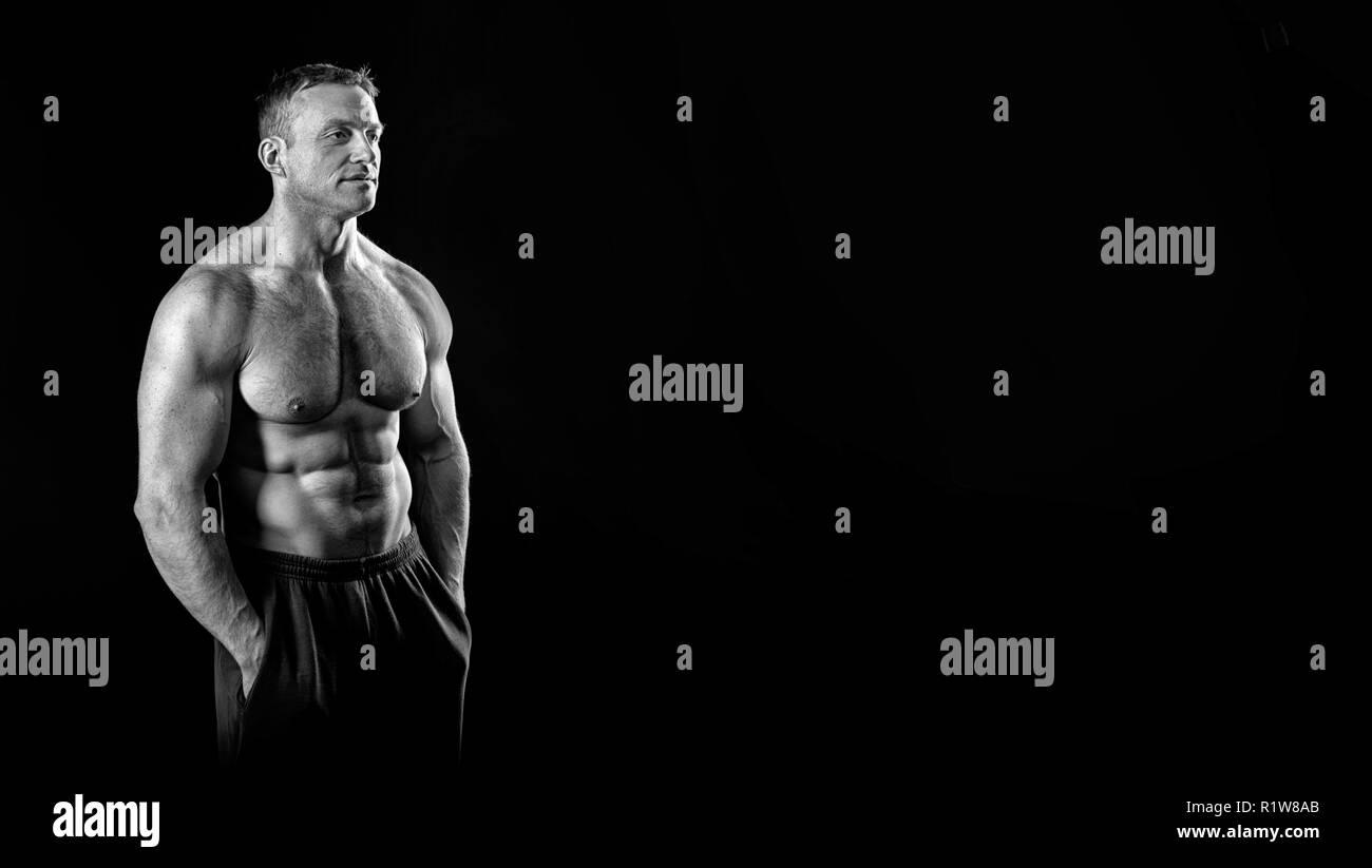 Concetto di bodybuilding. Forte culturista atleticità uomo pongono dopo formazione bodybuilding, bianco e nero, copia spazio. l'uomo. Forza e motivazioni. Immagini Stock