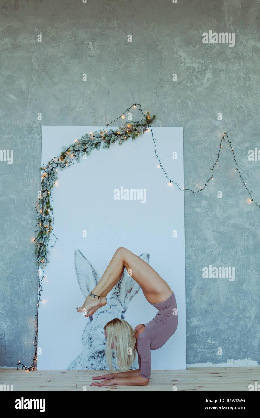 Vista laterale ritratto della bella slim giovane donna con il tatuaggio sul suo piede che lavora fuori, fare yoga o pilates esercizio. Scorpion pongono, vrischikasana. Fu Foto Stock
