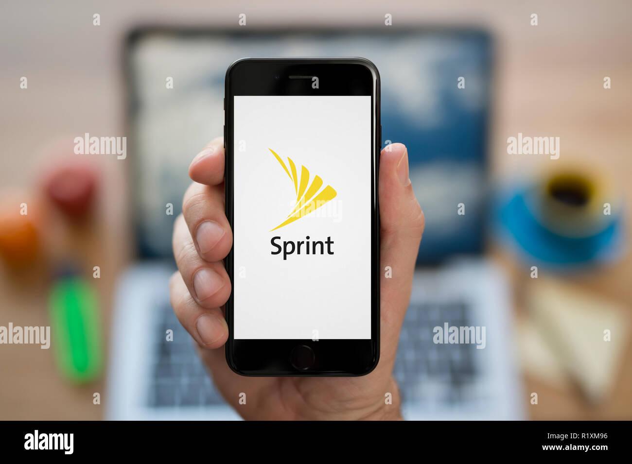 Un uomo guarda al suo iPhone che visualizza il logo Sprint, mentre se ne sta seduto alla sua scrivania per computer (solo uso editoriale). Immagini Stock