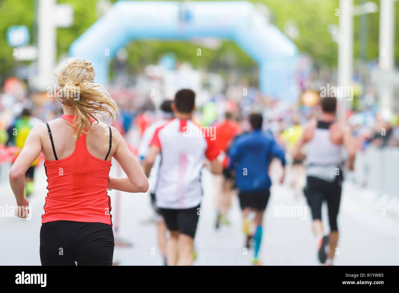 Esecuzione di donna e di fronte alla folla alla maratona di inizio o di fine linea Immagini Stock