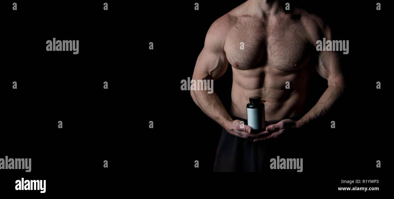 Concetto di vitamina. Vitamina bottiglia nelle mani muscolare. La terapia con Vitamina per il fitness e bodybuilding. La vitamina di cui avete bisogno per avere successo, copia dello spazio. Immagini Stock
