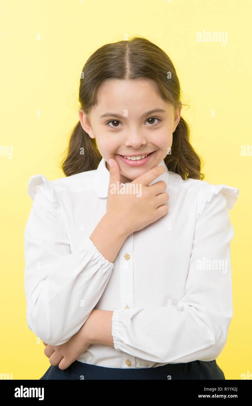 Ella è la pianificazione di una beffa. Scuola ragazza sorridente uniforme astuzia faccia sfondo giallo. Ragazza felice ritorno a scuola. Bambino pronto per tornare a scuola fine continuare il divertimento. La scolaretta abito formale sembra carino. Immagini Stock