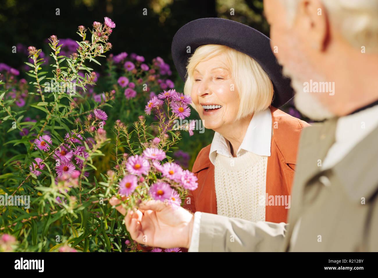 Positivo età felice donna godendo di odore di fiori Immagini Stock