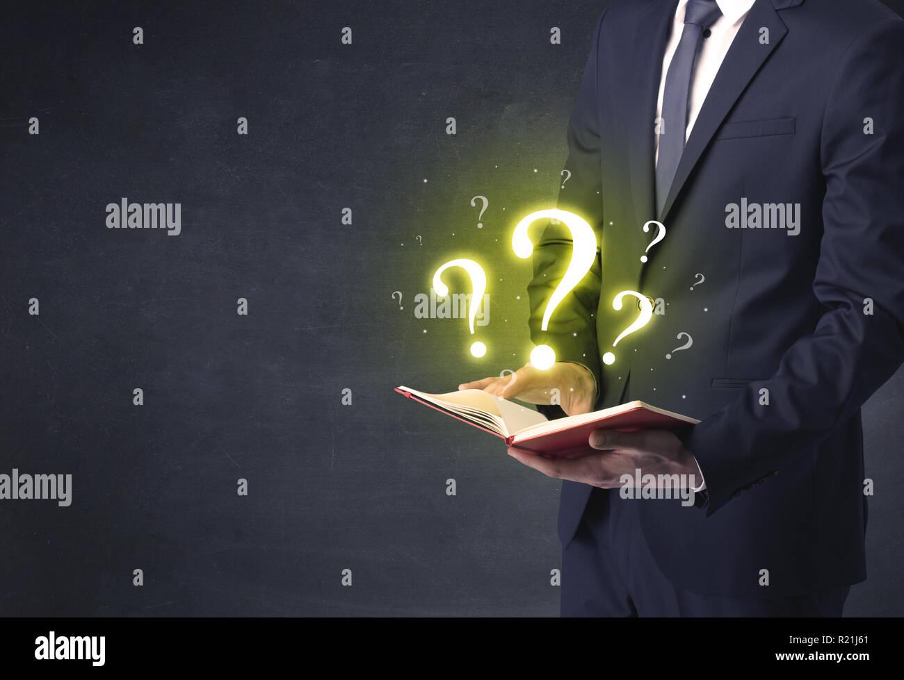 Imprenditore in possesso di un libro con punto interrogativo. Immagini Stock