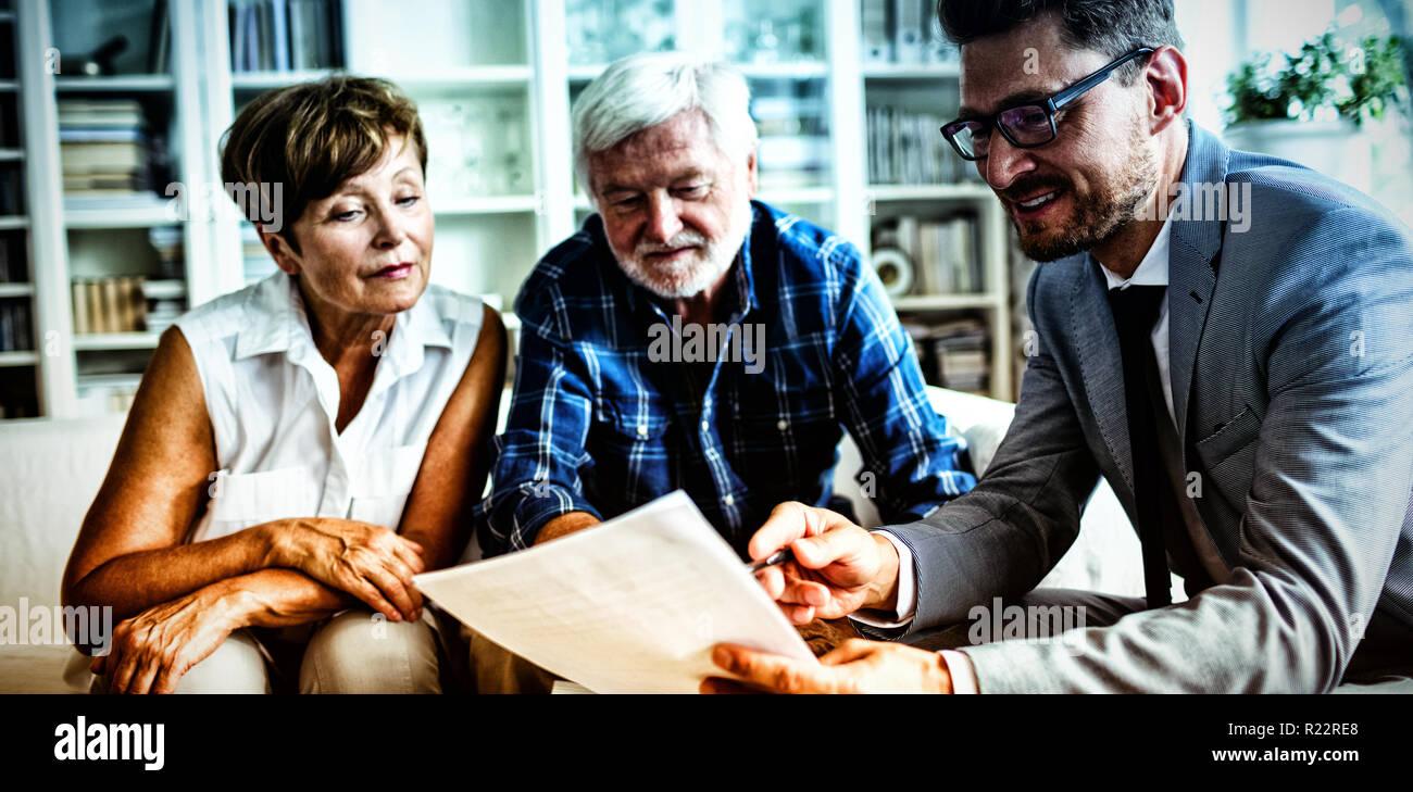 Coppia senior pianificare i loro investimenti con il consulente finanziario Immagini Stock
